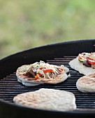 Mini vegetable pizzas on a barbecue
