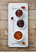 Three types of jam in bowls with spoons on a board