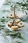 Jam sandwich biscuits on a cake stand between olives sprigs on a table covered with snow