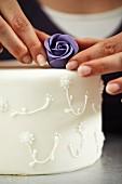 A confectioner decorating a wedding cake
