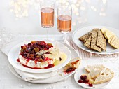 Baked brie with cranberries served with crackers and bread for Christmas
