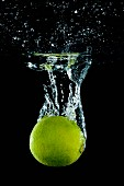 A lime falling into water with a splash