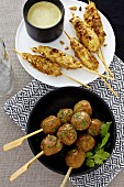 Chicken satay with peanut sauce and chicken meatballs kebabs with coriander (Asia)