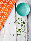 A blue bowl on a white shabby wooden table with a bright orange napkin and chopped parsley