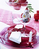 Festive place setting with red glass dishes embellished with Christmas tree decorations