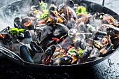 Steaming mussels with spices and chilli rings