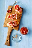 Sliced baguette topped with Serrano ham, grilled peppers and hot tomato salsa