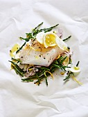 Cod on parchment paper with seaweed, fennel and lemon