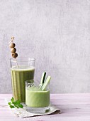 Two green smoothies garnished with olives and cucumber sticks