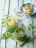 Two green smoothies garnished with citrus skewers and lamb's lettuce