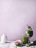 Two green smoothies garnished with figs and leaves