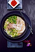 Udon noodle soup with pork, bok choy, spring onions and sesame (Japan)