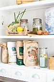 Various recycled paper bags, storage jars and fruit crates on kitchen shelves