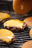 A hamburger with melting cheese on a grill