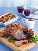 Roast leg of lamb with a side of vegetables, gravy and wine