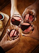 People toasting with glasses of mulled wine with apple and cinnamon