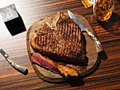 Sliced grilled T-bone steak on a wooden plate with a steak knife