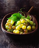 Green grapes in a vintage wooden bowl