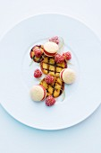 Grilled peach with ice cream macaroons and raspberries