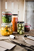 A selection of jars with pesto, ketchup, piccalilli, chutney and gherkins