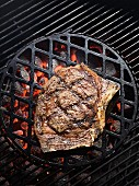 A rib-eye steak on a barbecue
