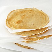 A stack of pancakes separated by sheets of parchment paper