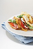 Pancakes with beefsteak, tomatoes, onion and rocket