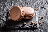 Macaroons with coffee beans on a black stone