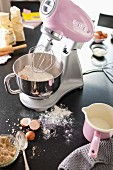 A pink Kitchen Aid working with a stainless steel mixing bowl of ingredients on a black surface