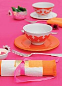 Orange place settings and matching napkins on hot-pink tablecloth