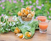 Physalis and fruit juice on a garden table