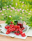 Redcurrants and a jar of redcurrant jam on a garden table