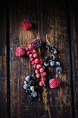 Frozen redcurrants, blackcurrants, raspberries and blackberries on a wooden surface