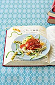 Various types of pasta with tomato sauce and green courgette strips on an open book