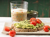 Avocado cream with cherry tomatoes on wholemeal bread served with a glass of cocoa