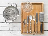 Kitchen utensils: a pot, a measuring jug, a citrus juicer, cutlery, a grater and a peeler