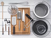 Kitchen utensils: a pan, a pot, a sieve, a grater, knives, cutlery and a measuring jug
