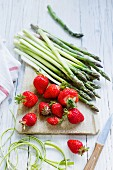 An arrangement of fresh strawberries and green asparagus on a wooden board