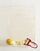 Potatoes, potato peelings and a peeler