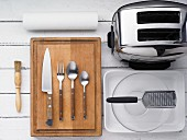 Kitchen utensils: a pastry brush, a knife, cutlery, a grater, a baking dish and toaster