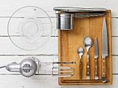 Various kitchen utensils: a mixer, a potato press, a citrus juicer and cutlery