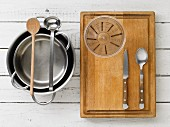 Kitchen utensils: saucepans, a ladle, a wooden spoon, a measuring cup and cutlery