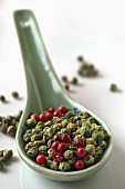 Green and red peppercorns on a ceramic spoon