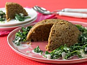 Almond nut roast on a bed of leaf spinach