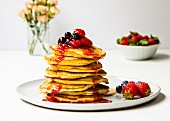 A pile of pancakes with berries and maple syrup
