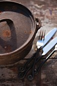A rustic cast-iron saucepan and cutlery on a wooden table