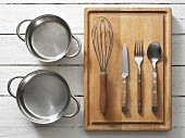 Assorted kitchen utensils: saucepans, cutlery and a whisk