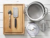 Assorted kitchen utensils: a grater, a sieve, a saucepan and a chopper