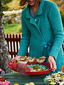 A woman serving mushroom soup at an alfresco autumnal buffet