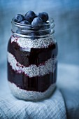Chia pudding with blueberries layered in a screw top glass (Superfood)